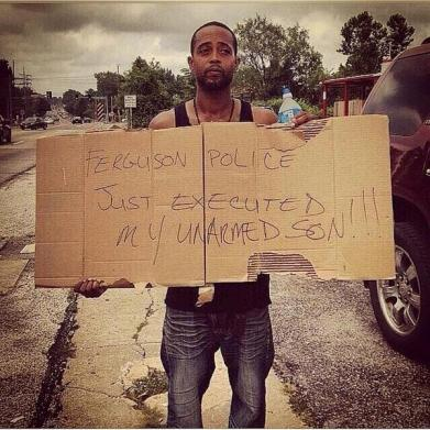 "Michael Brown's stepfather holds a sign which reads, ""Ferguson Police Just Executed My Unarmed Son!!!"""
