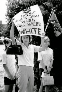 A woman stands on the side of the road challenging civil rights marchers with a hand written sign. Bogalusa, Louisiana, in 1965. Photograph by Matt Herron